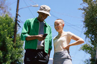 Young man and female friend looking at smartphone in suburbs, Los Angeles, California, USA - CUF48684