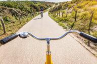 Cycling along rural road between dunes near Den Haag, personal perspective,  Scheveningen, South Holland, Netherlands - CUF48771