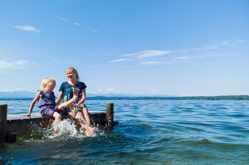 Mother and daughter cooling feet in water, Lake Starnberg, Bavaria, Germany - CUF48822