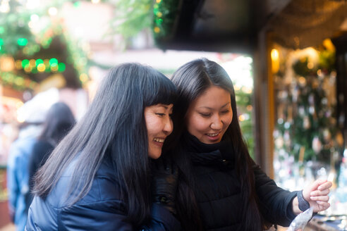 Mother and daughter window shopping at Christmas market, Freiburg, Baden-Wurttemberg, Germany - CUF48831