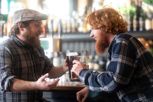 Two male customers making a toast in traditional Irish public house - CUF48846