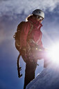 Mountain climber ascending mountain in bright sunlight, Chamonix, Rhone-Alps, France - CUF48930