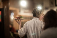 Waitress serving plate of burger in gastro pub - CUF48933