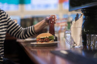Woman with plate of burger on pub counter top - CUF48936