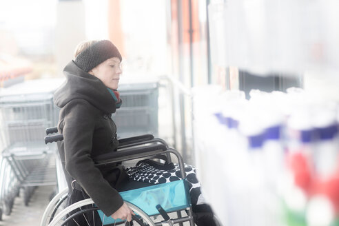 Woman in wheelchair going into supermarket - CUF48951