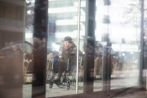 Reflection of woman in wheelchair on glass windows of building - CUF48954