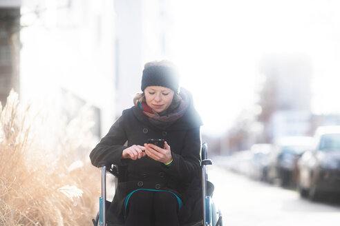 Woman in wheelchair using cellphone in street - CUF48957