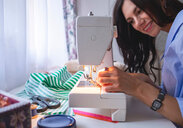 Woman threading sewing machine needle beside window - CUF48981