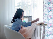 Woman using sewing machine beside window - CUF48984
