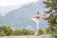 Woman practicing yoga, balancing on one leg on top of plinth, mountain landscape, Domodossola, Piemonte, Italy - CUF49008