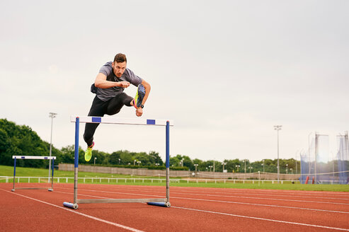 Athlete jumping over hurdle on running track - CUF49068