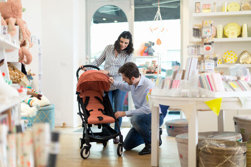 Husband and pregnant wife shopping for pram - CUF49089