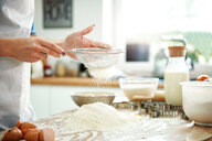 Woman sifting flour in kitchen - CUF49122