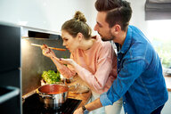 Couple tasting tomato soup in kitchen - CUF49125