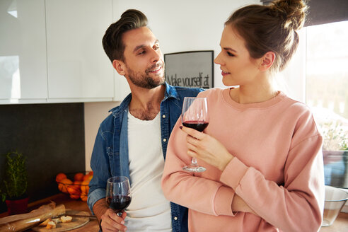 Couple talking and drinking red wine in kitchen - CUF49128