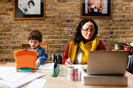 Toddler boy learning from mother working from home - CUF49152
