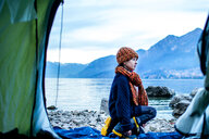 Boy outside tent on lakeside, Lake Como, Onno, Lombardy, Italy - CUF49155