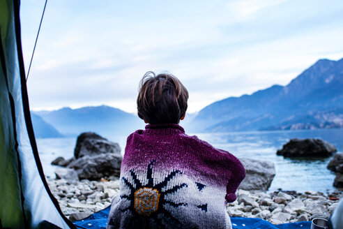 Boy looking out over lake from tent, rear view, Lake Como, Onno, Lombardy, Italy - CUF49158