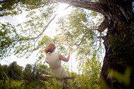 Woman on swing in forest - CUF49218