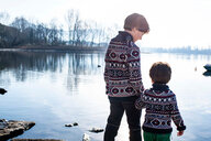 Boy and toddler brother in matching sweaters standing on lakeside, Lake Como, Lecco, Lombardy, Italy - CUF49221