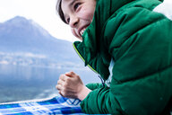 Boy in green anorak lying on picnic blanket by lakeside, cropped, Lake Como, Onno, Lombardy, Italy - CUF49224