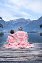 Boy and father wrapped in blanket on lakeside pier, rear view, Lake Como, Onno, Lombardy, Italy - CUF49227