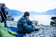 Father and son camping by lakeside, Onno, Lombardy, Italy - CUF49233