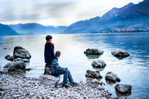 Father and son on lakeside, Onno, Lombardy, Italy - CUF49236