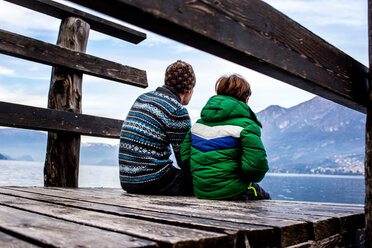 Boy and father sitting on lakeside pier, rear view, Lake Como, Onno, Lombardy, Italy - CUF49251