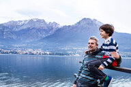 Boy and father sitting on pier fence, Lake Como. Onno, Lombardy, Italy - CUF49254