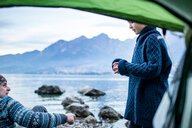 Father and son camping on lakeside, view from inside tent, Onno, Lombardy, Italy - CUF49257