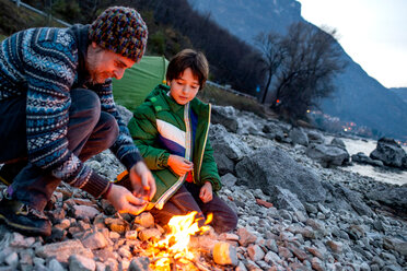 Father and son toasting marshmallows over campfire, Onno, Lombardy, Italy - CUF49260