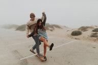Young couple holding hands sharing a skateboard in beach carpark, Jalama, California, USA - ISF20551