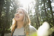Curious teenage girl hiking, looking up at tress in woods - HEROF20676