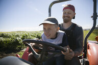 Father farmer and son driving tractor on sunny farm - HEROF20694