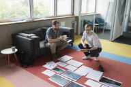 Creative male designers reviewing paperwork and proofs on office floor - HEROF20727