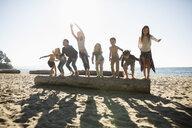 Exuberant boy and girl friends jumping off log on sunny ocean beach - HEROF20850