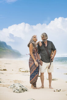 Senior hippie couple with guitar standing on the beach - SBOF01702