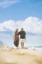 Senior hippie couple with guitar strolling arm in arm on the beach - SBOF01705
