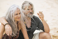 Portrait of senior hippie couple smoking on the beach - SBOF01708