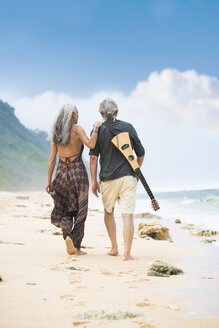 Back view of senior hippie couple with guitar strolling side by side on the beach - SBOF01711
