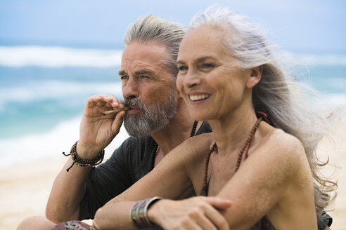 Senior hippie couple relaxing together on the beach - SBOF01717