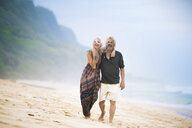 Happy senior hippie couple strolling side by side on the beach - SBOF01720