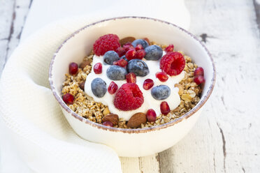 Bowl of muesli with Greek yogurt, popped quinoa, raspberries, blueberries and pomegranate seed - LVF07769