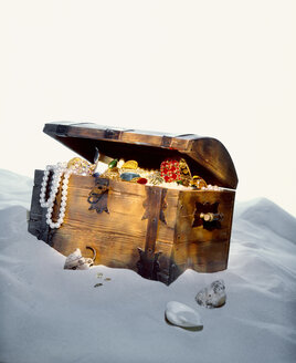 Treasure chest filled with jewels on sandy beach - PPXF00146
