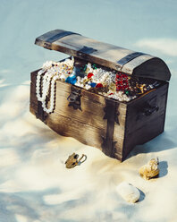 Treasure chest filled with jewels and gold coins on sandy beach - PPXF00173
