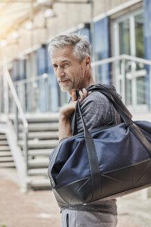 Deutschland, NRW, Düsseldorf, Lifestyle, Sport, GYM, Best Ager mit Sporttasche vor dem GYM - RORF01719