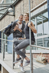 Portrait of mature man with sports bag and young woman in front of gym watching something - RORF01725
