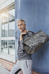 Portrait of mature man with camouflage sports bag standing in front of gym - RORF01728