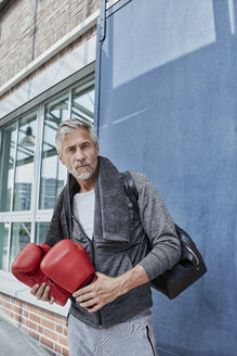 Portrait of mature man with towel, sports bag and red boxing gloves standing in front of gym - RORF01731